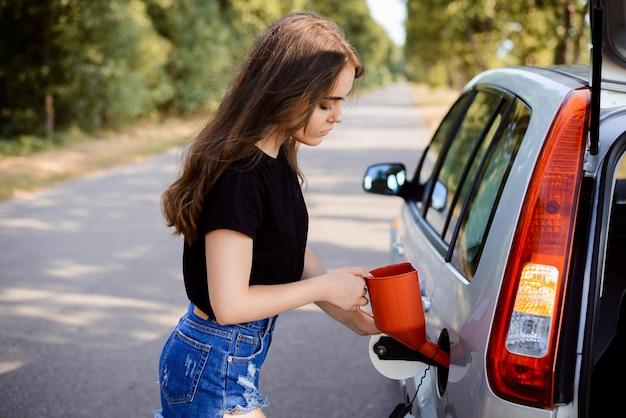 Attraktives mädchen öffnet den deckel des kraftstofftanks im auto und setzt roten bailer nach innen, um den tank zu tanken. konzept des füllens des kraftstofftanks in der reise Premium Fotos