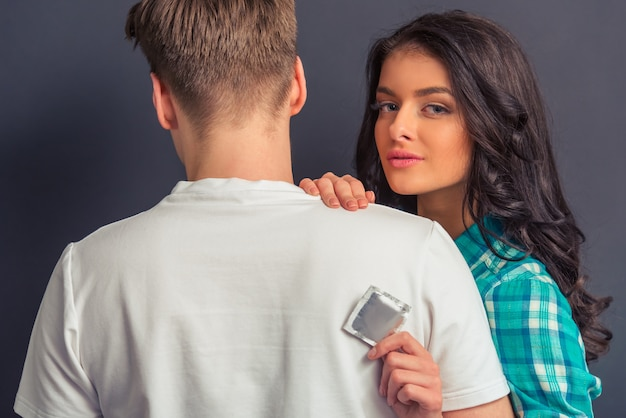 Attraktives mädchen zeigt ein kondom und betrachtet kamera. Premium Fotos