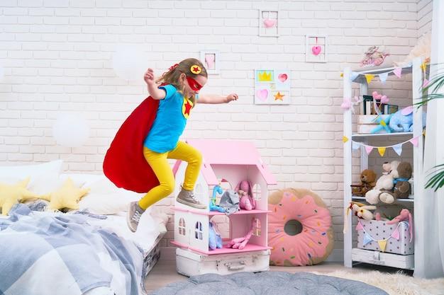 Attraktives nettes kleines mädchen springt vom bett, um zu fliegen, wenn sie superheld spielt Premium Fotos