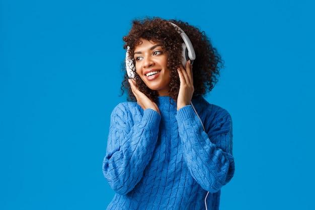 Attraktives sinnliches afroamerikanisches weibliches mädchen mit afro-haarschnitt, winterpullover tragend, mit angenehmem lächeln nach links schauend, kopfhörer tragend, hört lieder. Kostenlose Fotos