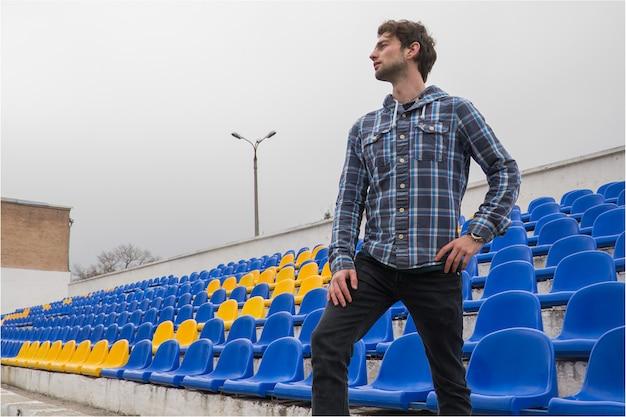 Attraktives sportliches modell des jungen mannes im blauen hemd, das auf blauen stadionsitzen nach dem training anstarrt entlang des feldes sitzt Premium Fotos