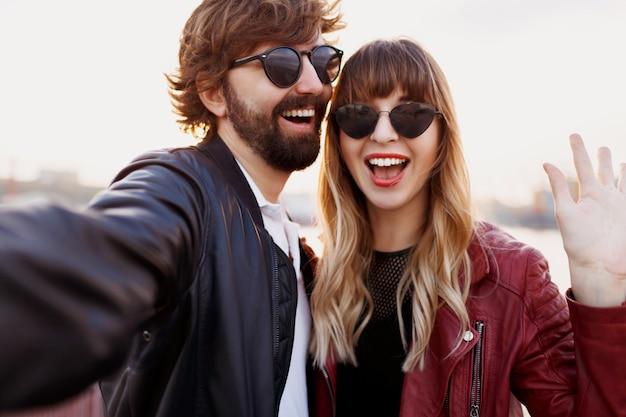 Attraktives stilvolles paar in der liebe, die im freien aufwirft, umarmt und auf kai geht. weiche abendfarben. modischer look. trendige sonnenbrille. mann und frau peinlich. Kostenlose Fotos