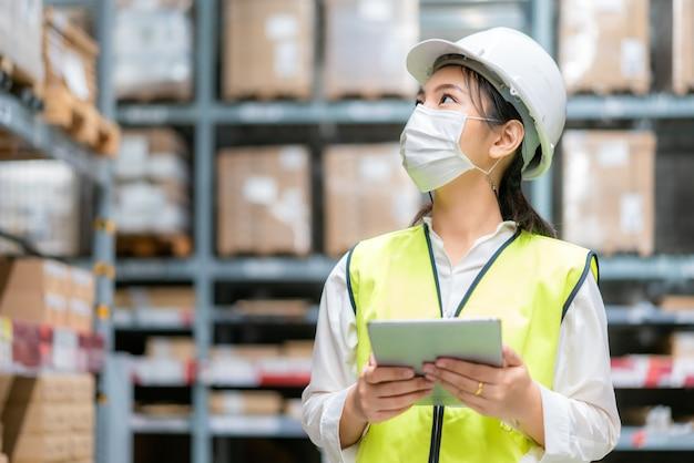 Auditorin oder auszubildende der jungen frau trägt eine maske, die während der covid-pandemie im lager arbeitet Premium Fotos