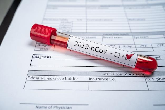 Auf dem formular zur aufzeichnung der diagnose liegt ein reagenzglas mit einem positiven test auf ein neues coronavirus aus china. Premium Fotos