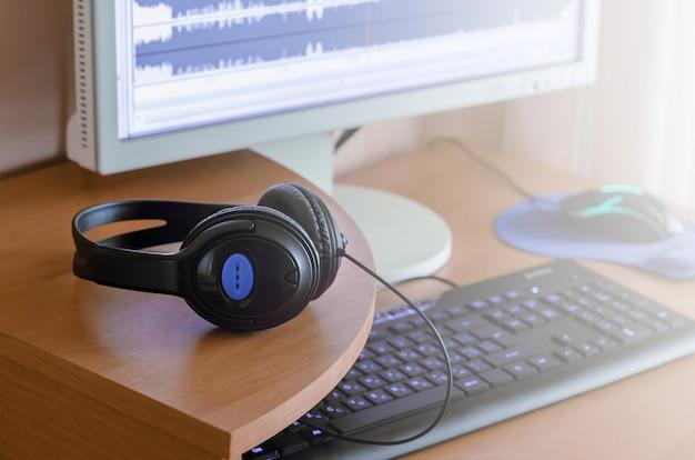 Auf dem hölzernen desktop des sounddesigners liegen große schwarze kopfhörer Premium Fotos