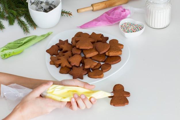 Auf dem küchentisch auf einem teller lebkuchen, fichtenzweige, mehl, zuckerguss, zucker und hände eines jungen, der kekse verziert Premium Fotos