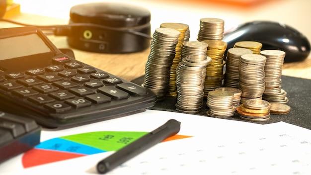 Auf dem schreibtisch münzenstapel, taschenrechner, tastatur, finanzbudget, grafiken und briefpapier Premium Fotos