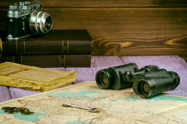 Auf dem tisch lagen ein altes buch, eine karte, münzen, ein schlüssel und ein fernglas, und es gibt eine filmkamera. Premium Fotos