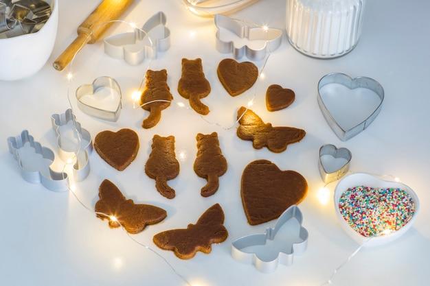 Auf dem tisch sind aus ingwertig schmetterlinge, katzen, herzen, dekor zum dekorieren von keksen, girlanden geschnitzt Premium Fotos