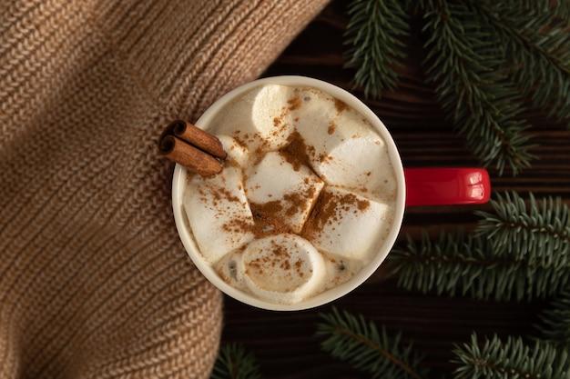 Auf dem tisch steht eine tasse heiße schokolade mit marshmallows mit weihnachtsdekoration Premium Fotos