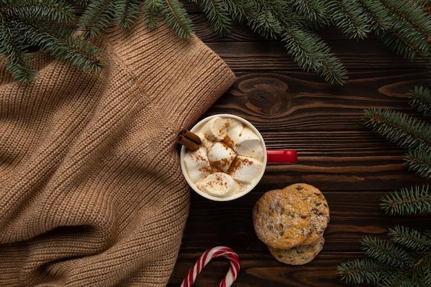 Auf dem tisch steht eine tasse heiße schokolade mit marshmallows und hausgemachten keksen mit weihnachtsdekoration. Premium Fotos