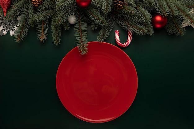 Auf dem weihnachtstisch steht ein leerer roter teller. Premium Fotos
