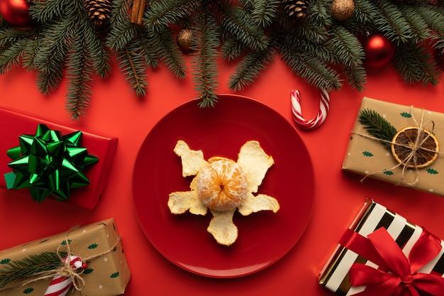 Auf dem weihnachtstisch steht ein teller mit mandarinen Premium Fotos