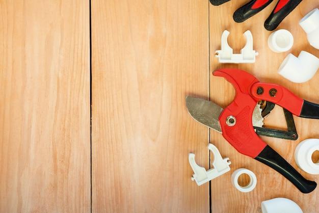 Auf einem holzplatz befinden sich werkzeuge zur reparatur von kunststoffrohren. Premium Fotos