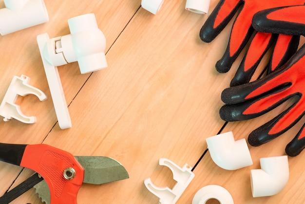 Auf einem holztisch befindet sich zubehör zur reparatur von wasserleitungen. Premium Fotos