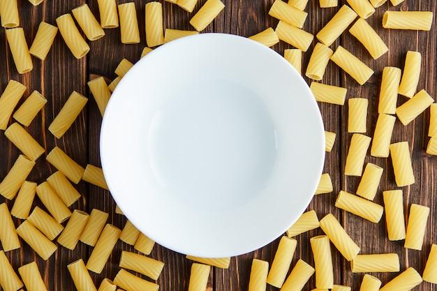 Auf einem holztisch lagen tortiglioni-nudeln mit leerem teller flach Kostenlose Fotos