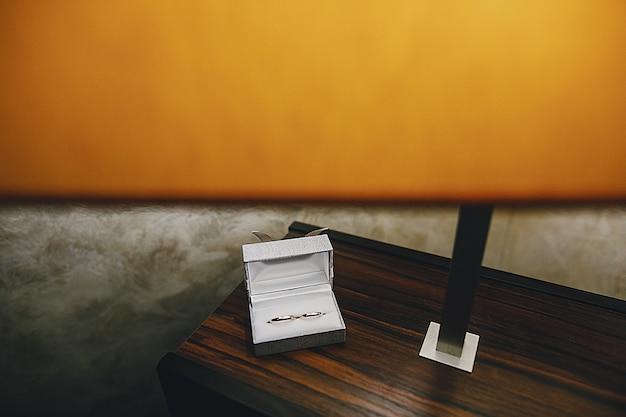 Auf einem holztisch neben einer tischlampe befindet sich eine weiße box mit trauringen Kostenlose Fotos