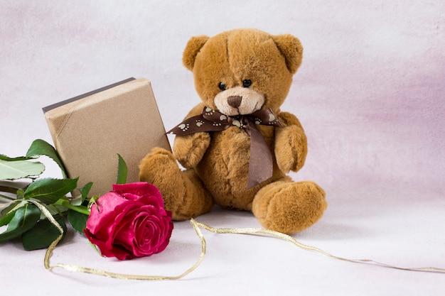 Auf einem rosafarbenen hintergrund, einer hellen rosafarbenen rose, einem spielzeugbären und einer geschenkbox Premium Fotos