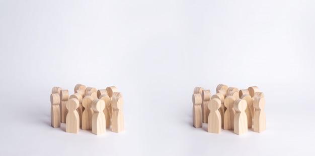 Auf einem weißen hintergrund stehen zwei menschenmengen von holzfiguren von menschen. Premium Fotos