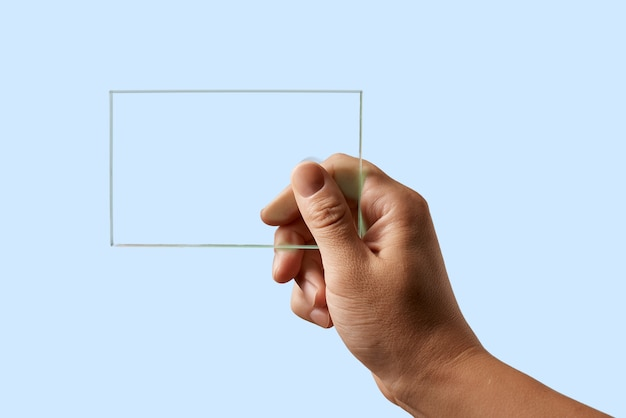 Auf einer blauen oberfläche hält die hand eines mannes ein transparentes glas v Premium Fotos