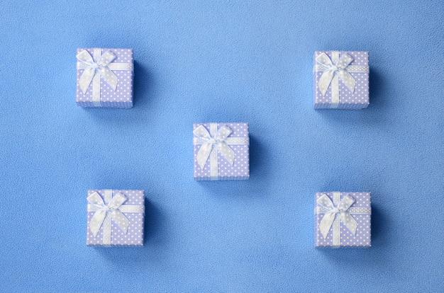 Auf einer decke liegen viele kleine geschenkboxen in blauer farbe mit kleiner schleife Premium Fotos