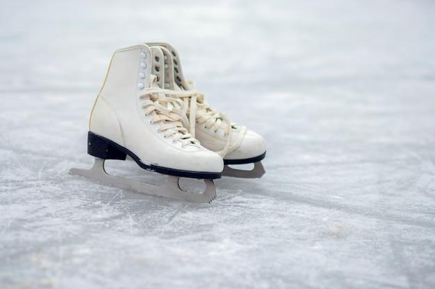 Auf einer offenen eisbahn stehen zwei weiße eiskunstläufer. wintersport Premium Fotos