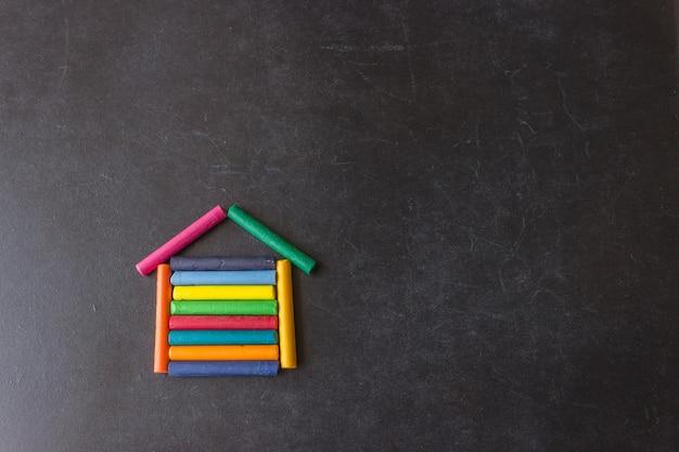 Auf einer schwarzen schultafel sind helle pastellstifte in form eines hauses angeordnet. kreativität für kinder. hintergrund mit exemplar Premium Fotos