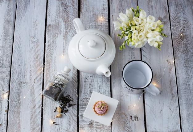 Auf weißer holztischschale, teekanne, freesie und kuchen Premium Fotos