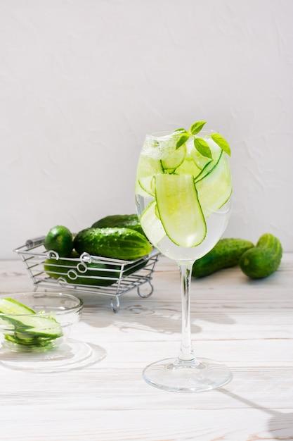Auffrischungswasser mit scheiben der gurke und des basilikums verlässt in einem glas Premium Fotos