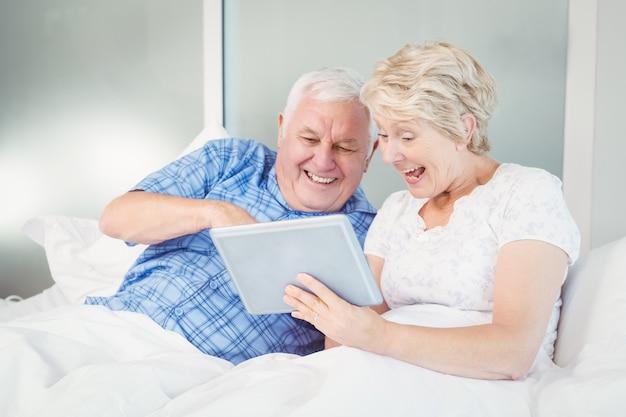 Aufgeregte ältere paare unter verwendung der digitalen tablette auf bett Premium Fotos