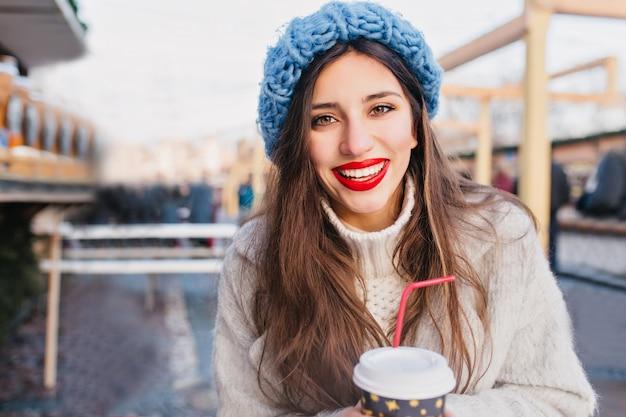 Aufgeregte brünette frau mit braunen augen, die tee auf unschärfestadt trinken. außenfoto der herrlichen dunkelhaarigen dame im mantel und im blauen hut, die tasse des heißen kaffees im kalten tag halten. Kostenlose Fotos
