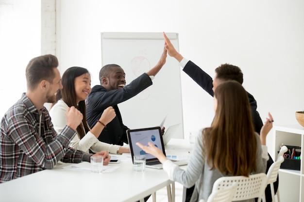 Aufgeregte diverse kollegen oder partner, die beim teammeeting high-five geben Kostenlose Fotos