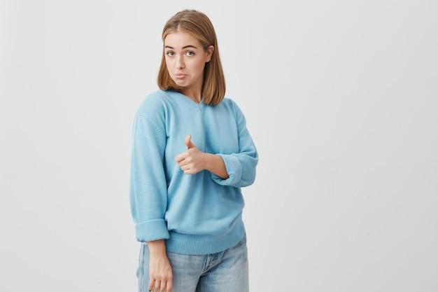 Aufgeregte emotionale junge europäische kundin mit hellem haar in blauen kleidern, die ihren daumen aufgibt und zeigt, wie gut ein produkt ist. gesten und körpersprache Kostenlose Fotos