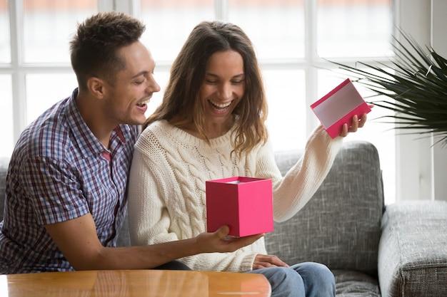 Aufgeregte eröffnungsgeschenkbox der jungen frau, die geschenk vom ehemann empfängt Kostenlose Fotos