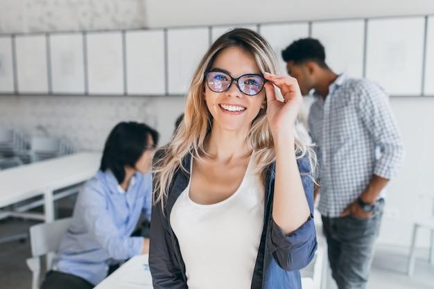 Aufgeregte europäische studentin, die eine brille hält und zwischen den vorlesungen posiert. innenporträt der lächelnden frau, die neben asiatischen und afrikanischen universitätskameraden während des seminars steht. Kostenlose Fotos