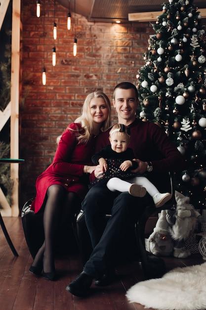Aufgeregte familie mit entzückendem baby am weihnachten Premium Fotos