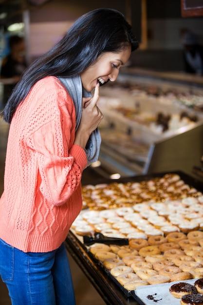 Aufgeregte frau, die donuts auswählt Premium Fotos