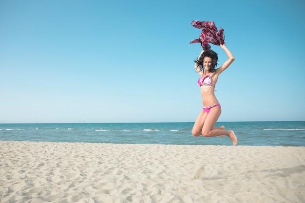 Aufgeregte frau im badeanzug, der auf den strand springt Kostenlose Fotos