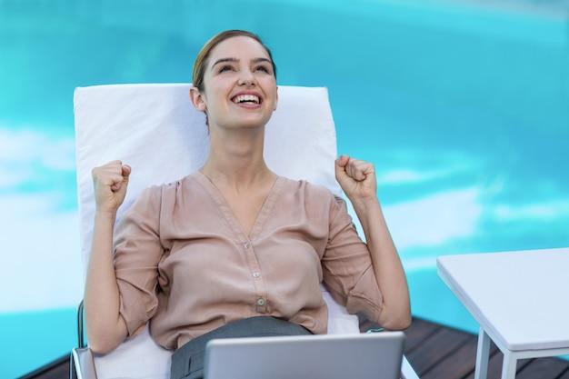 Aufgeregte frau mit laptop nahe pool Premium Fotos