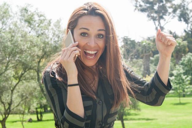Aufgeregte glückliche dame, die am telefon spricht und mit freude schreit Kostenlose Fotos