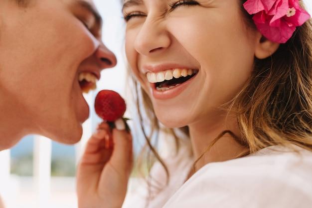 Aufgeregte glückliche junge frau mit niedlicher rosa blume im hellbraunen haar, das ihren lachenden ehemann mit frischer erdbeere füttert. nahaufnahmeporträt des romantischen genießens der flitterwochen und des essens von beeren Kostenlose Fotos