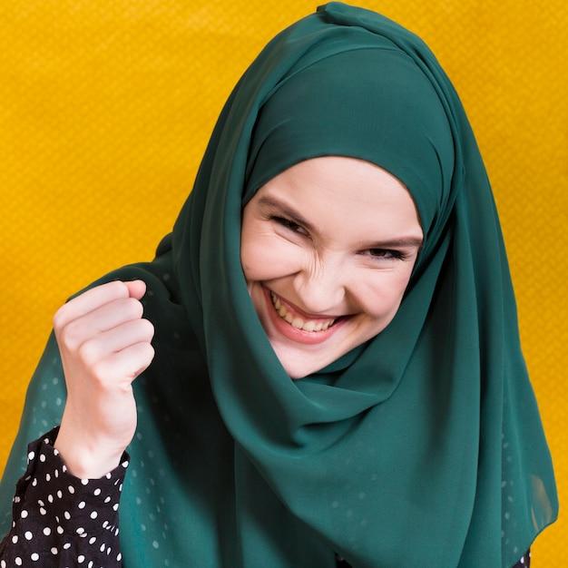 Aufgeregte glückliche moslemische junge frau, die kamera vor gelbem hintergrund betrachtet Kostenlose Fotos