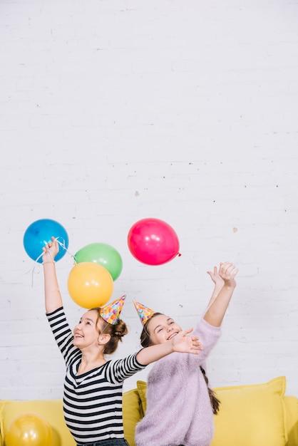 Aufgeregte jugendlichen, die ihre hände anhalten, die bunte ballone halten Kostenlose Fotos