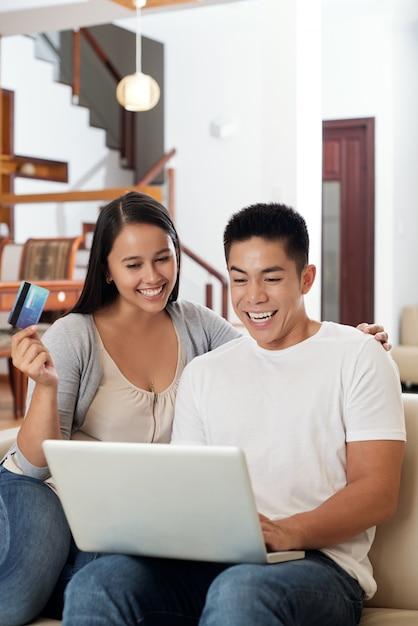 Aufgeregte junge asiatische paare, die zu hause auf couch mit laptop und kreditkarte sitzen Kostenlose Fotos