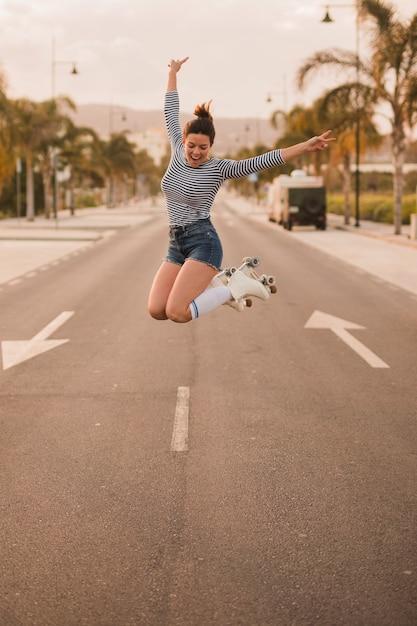 Aufgeregte junge frau, die den tragenden rollschuh des friedenszeichens springt auf straße gestikuliert Kostenlose Fotos