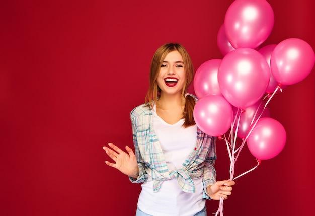 Aufgeregte junge frau, die mit rosa luftballons aufwirft Kostenlose Fotos