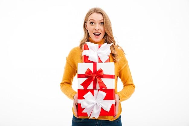 Aufgeregte junge frau, die überraschungsgeschenkboxen hält. Kostenlose Fotos