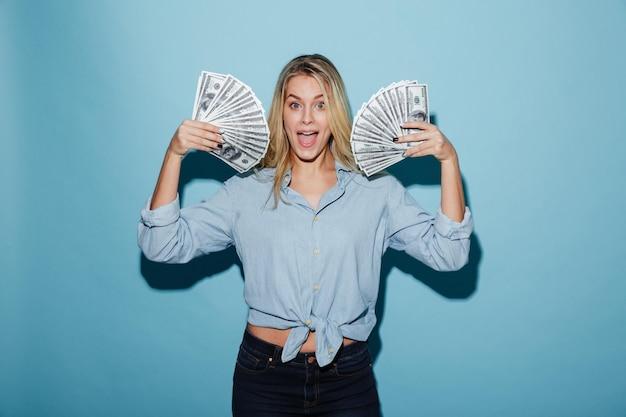 Aufgeregte junge hübsche blondine, die geld in den händen halten. Kostenlose Fotos