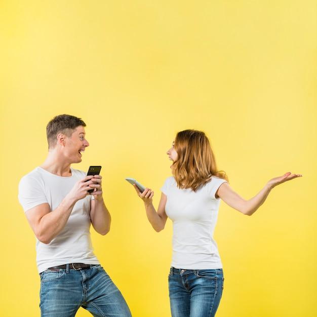 Aufgeregte junge paare, die in der hand den handy schreien mit freude halten Kostenlose Fotos