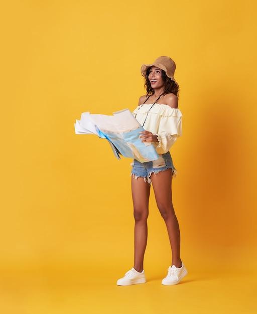 Aufgeregte junge schwarze frau kleidete in der sommerkleidung an, die reisekartenführer und -c $ schauen hält Premium Fotos
